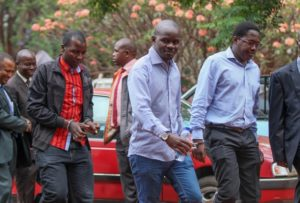 Journalists from the weekly Sunday Mail as they were arrested on Nov. 4, 2015 on charges of reporting falsehoods. Pictured from left to right in handcuffs are the journalists, who included the Sunday Mail reporter Tinashe Farawo, the paper's investigations editor Brian Chitemba and The Sunday Mail editor Mabasa Sasa. Credit: Jeffrey Moyo/IPS