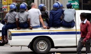 Activists in a police truck in Harare. They were detained before a protest against government plans to introduce a new currency. Photograph: Philimon Bulawayo/Reuters